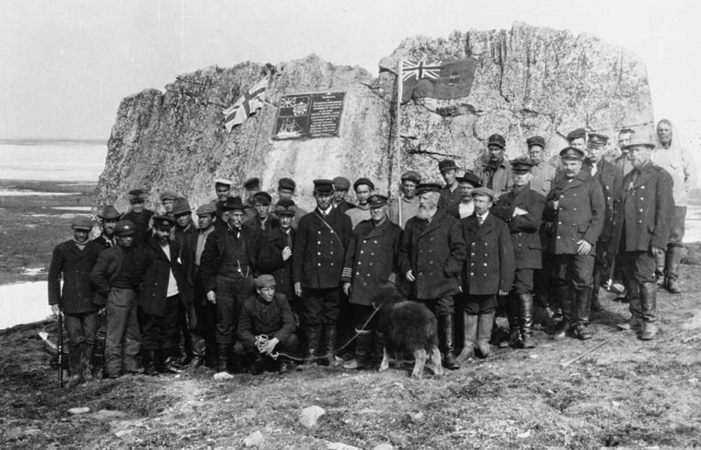 Historical image of a group of men in front of a sandstone monument used to guide explorers