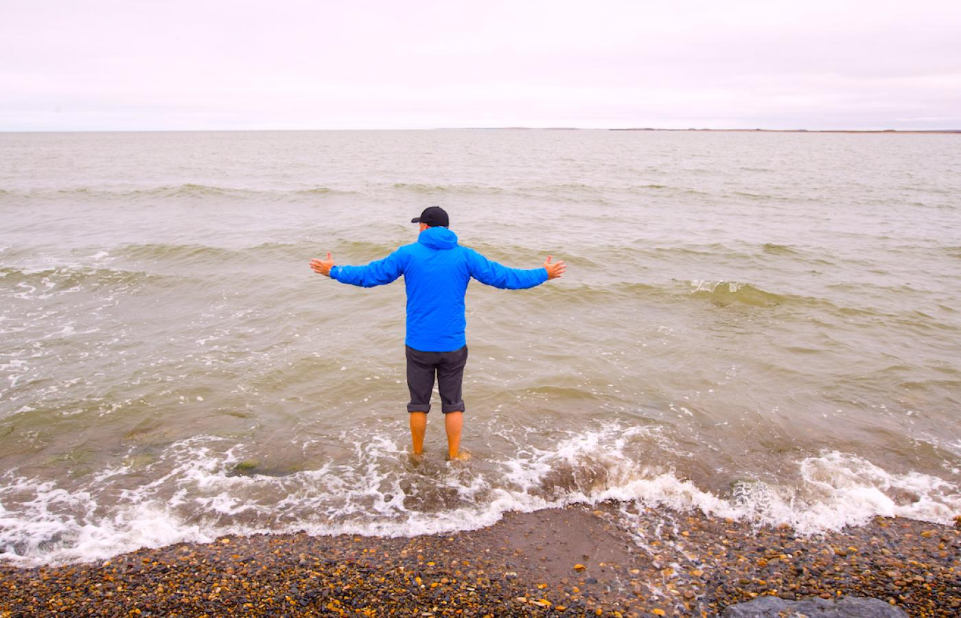 man wading into Arctic Ocean from Tuk