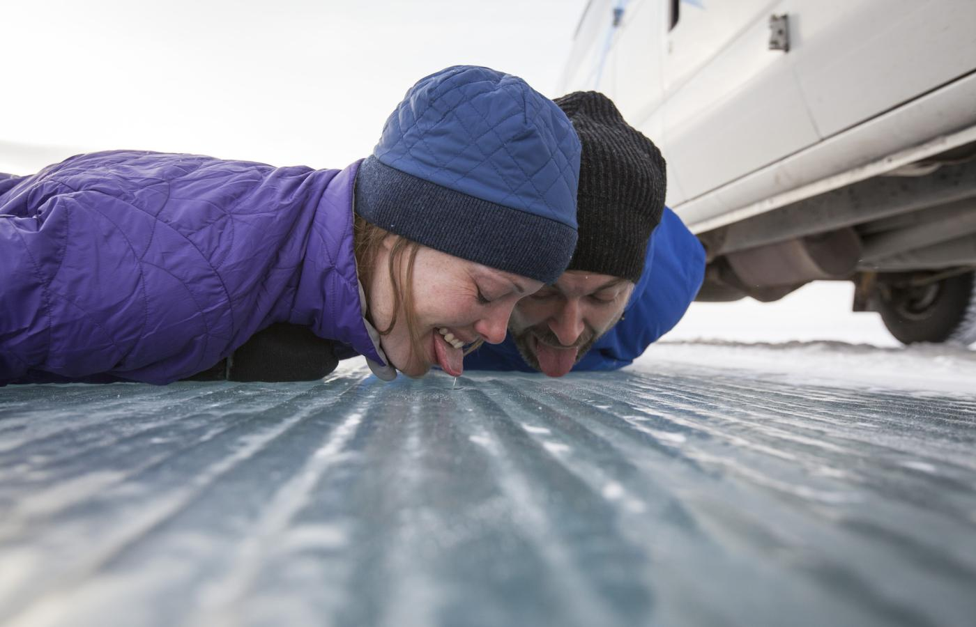 Two people sticking their tongues to the ice road in the NWT
