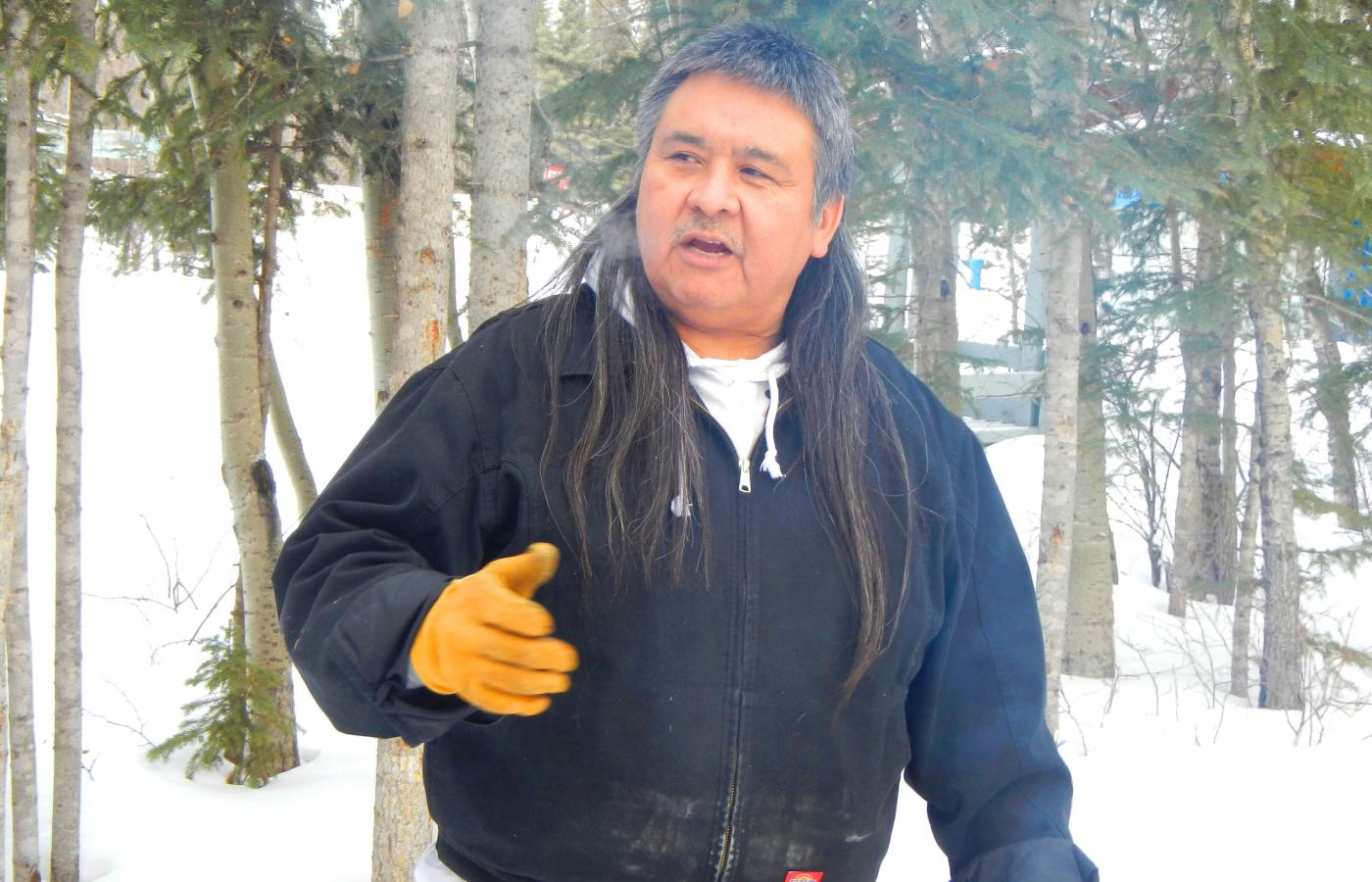 Dene elder shares a story around the campfire