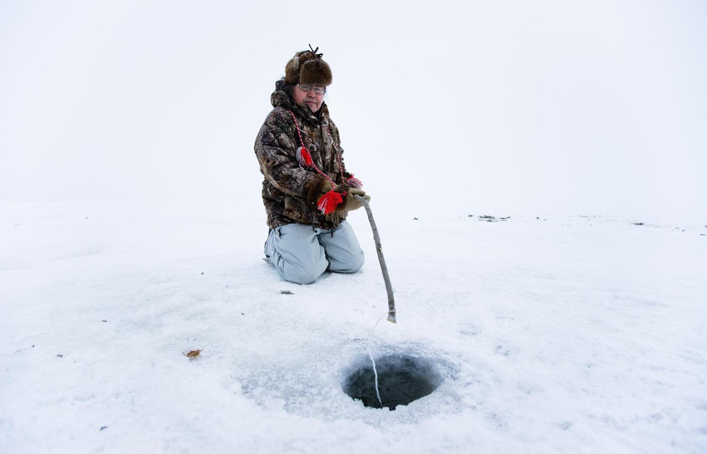 man ice fishing in the dehcho