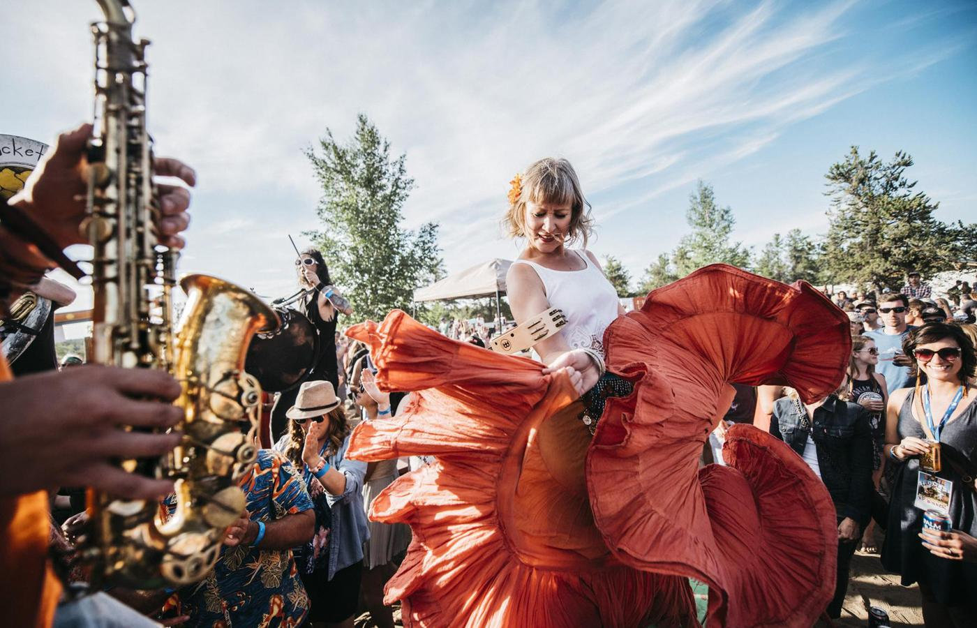 woman in a bright orange dress dances under the midnight sun at folk on the rocks