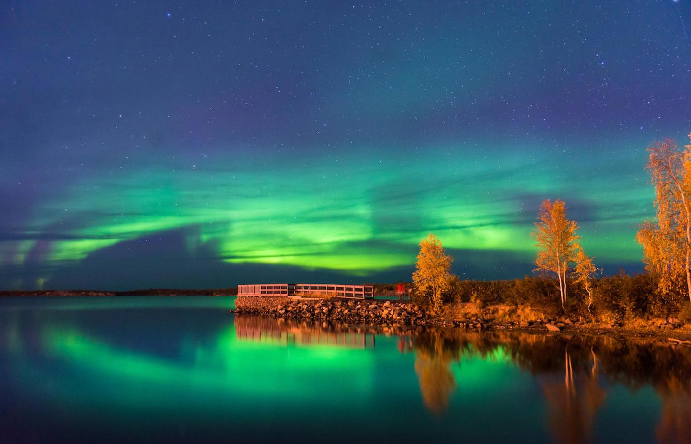 green northern lights dance across a lake in the summer