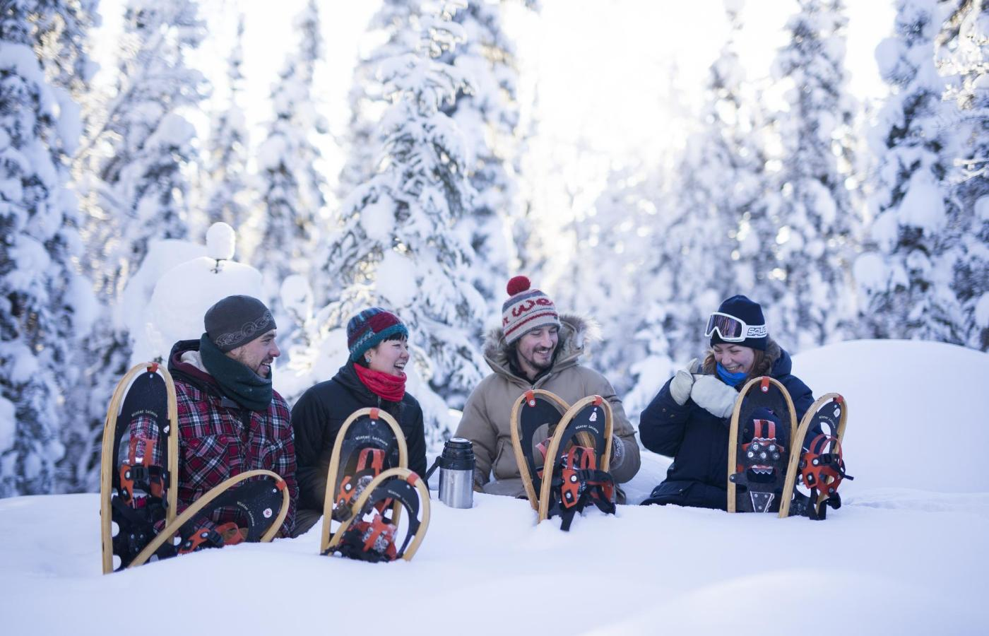 four friends sit in the snow sipping hot chocolate with snowshoes around them