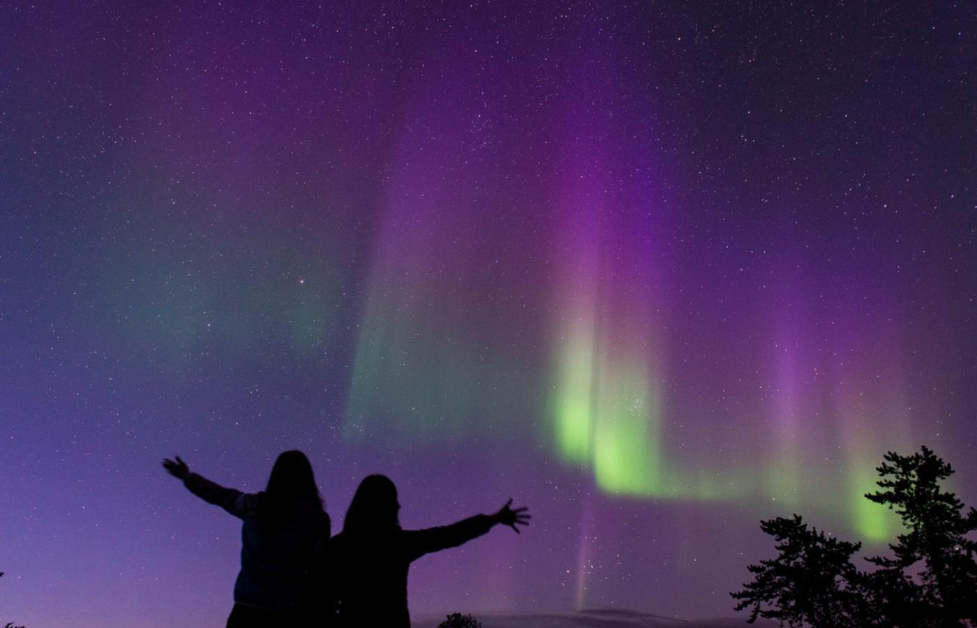 two people celebrate the NWT's northern lights