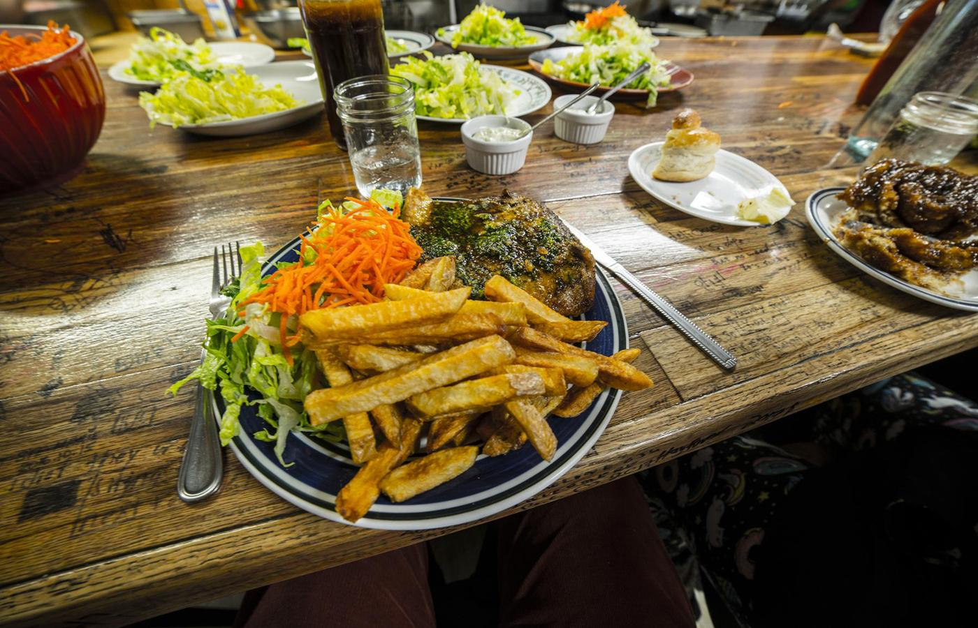 A large plate of fish and chips sits on a wood table looking delicious.