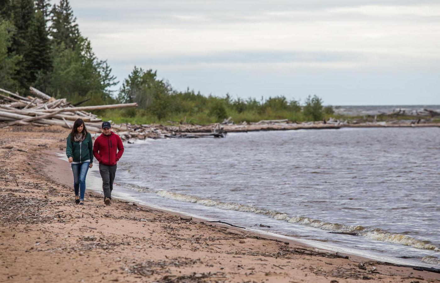 A man and woman walk along the sandy south shore of Great Slave Lake