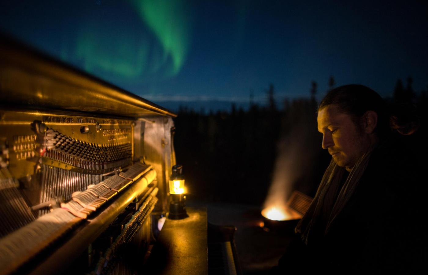 Roman Zavada sits at a piano outside in the dark. The green northern lights dance overhead.