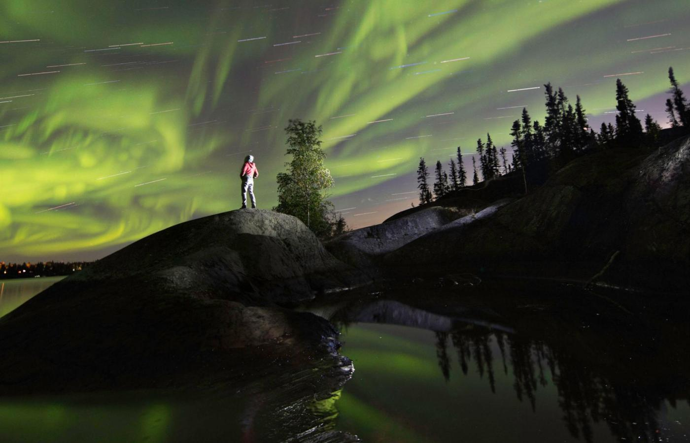 Amazing green Northern Lights illuminate the night sky over a lake in the NWT