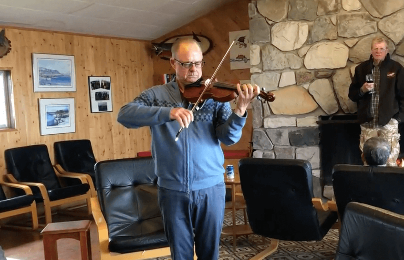 A man plays violin for other guests at an Arctic fishing lodge