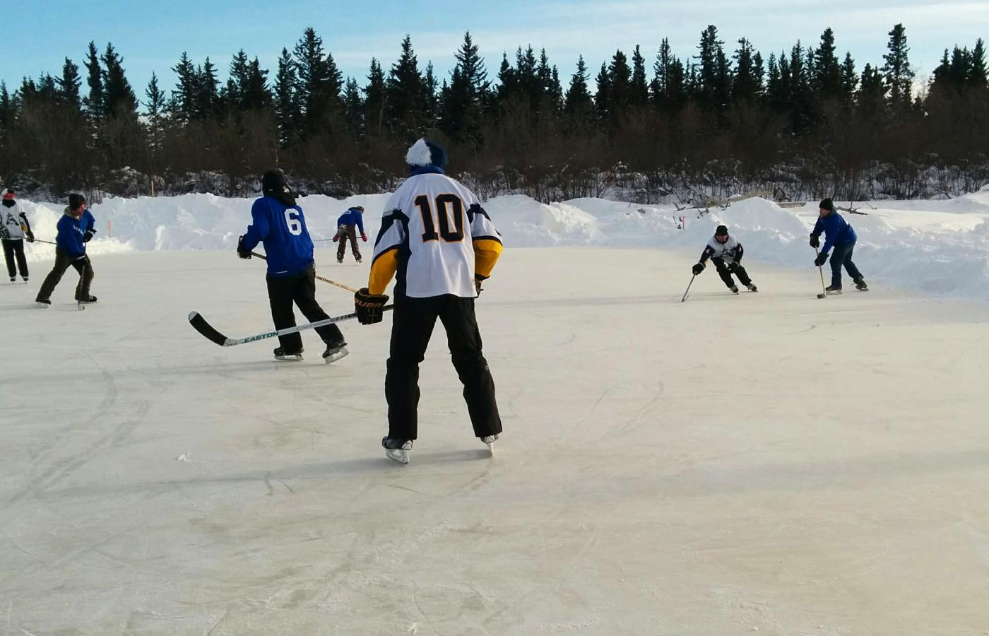 People playing hocket at the Polar Pond Hockey Tournament in Hay River, NWT.