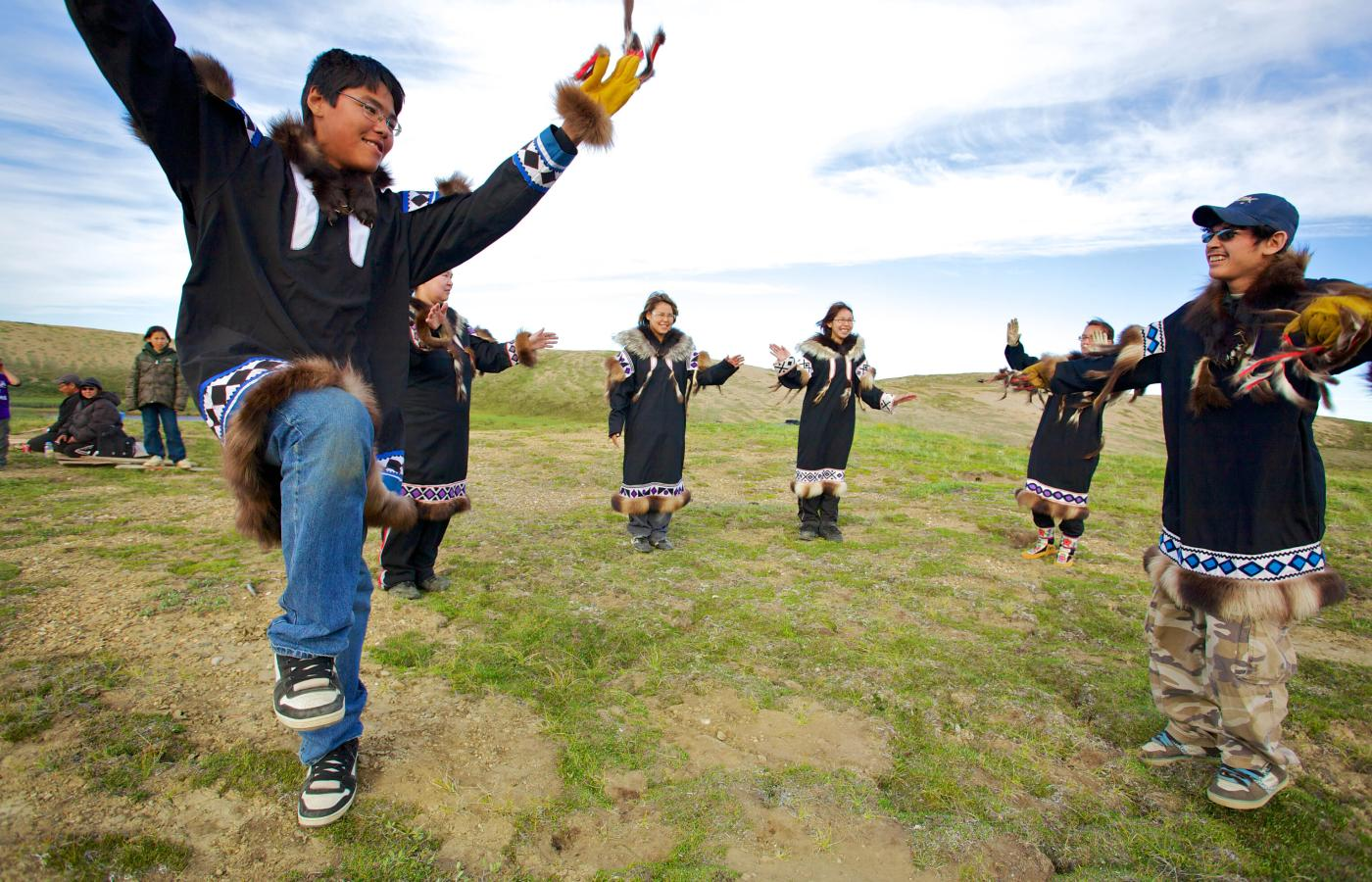 People dancing in teh grass with their arms up in the air on National Indigenous Peoples Day, a statutory holiday in the NWT.