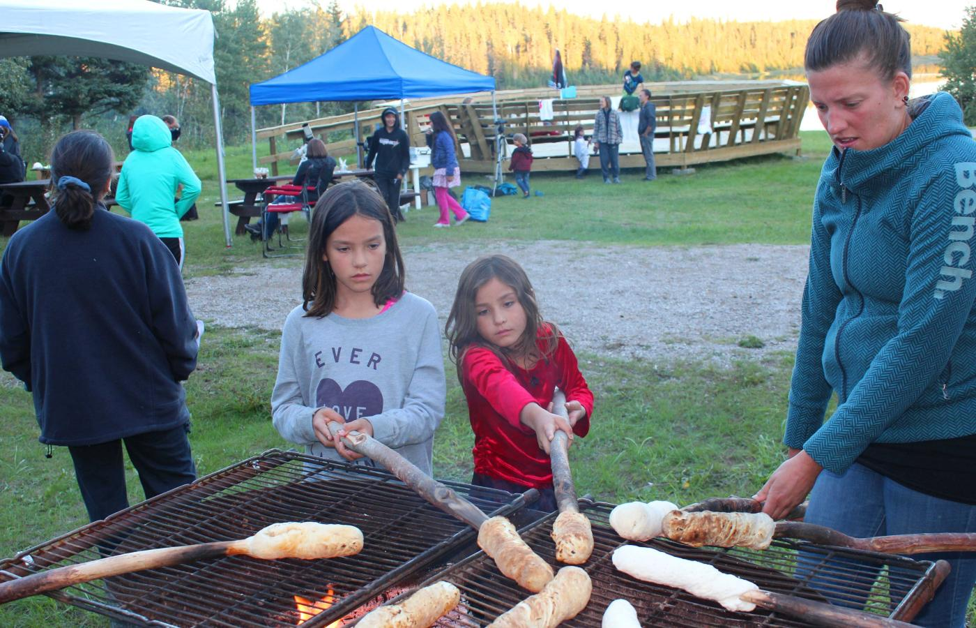 Two kids standing in front of a grill and cooking their bannock on a stick at the Dark Sky Festival in Fort Smith, NWT.