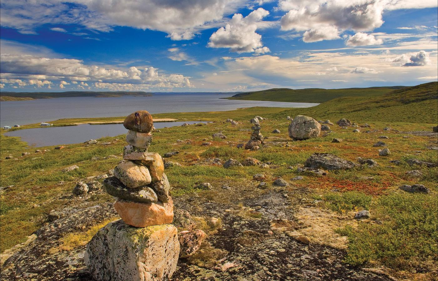 An Inukshuk stands on the tundra near the Arctic Ocean