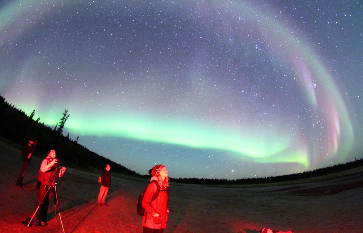 Three people stnding in the road watching the aurora over Fort Smith at the Dark Sky Festival in the NWT.