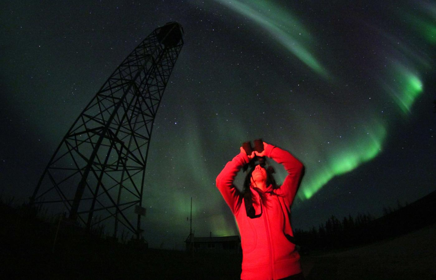 A man with his arms in the air watching the Aurora borealis over Fort Smith, NWT.