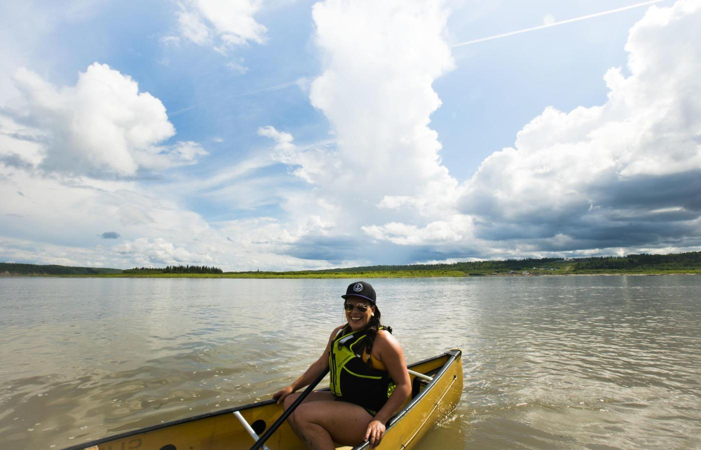 Woman relaxing in a canoe on the massive Mackenzie River near Fort Simpson