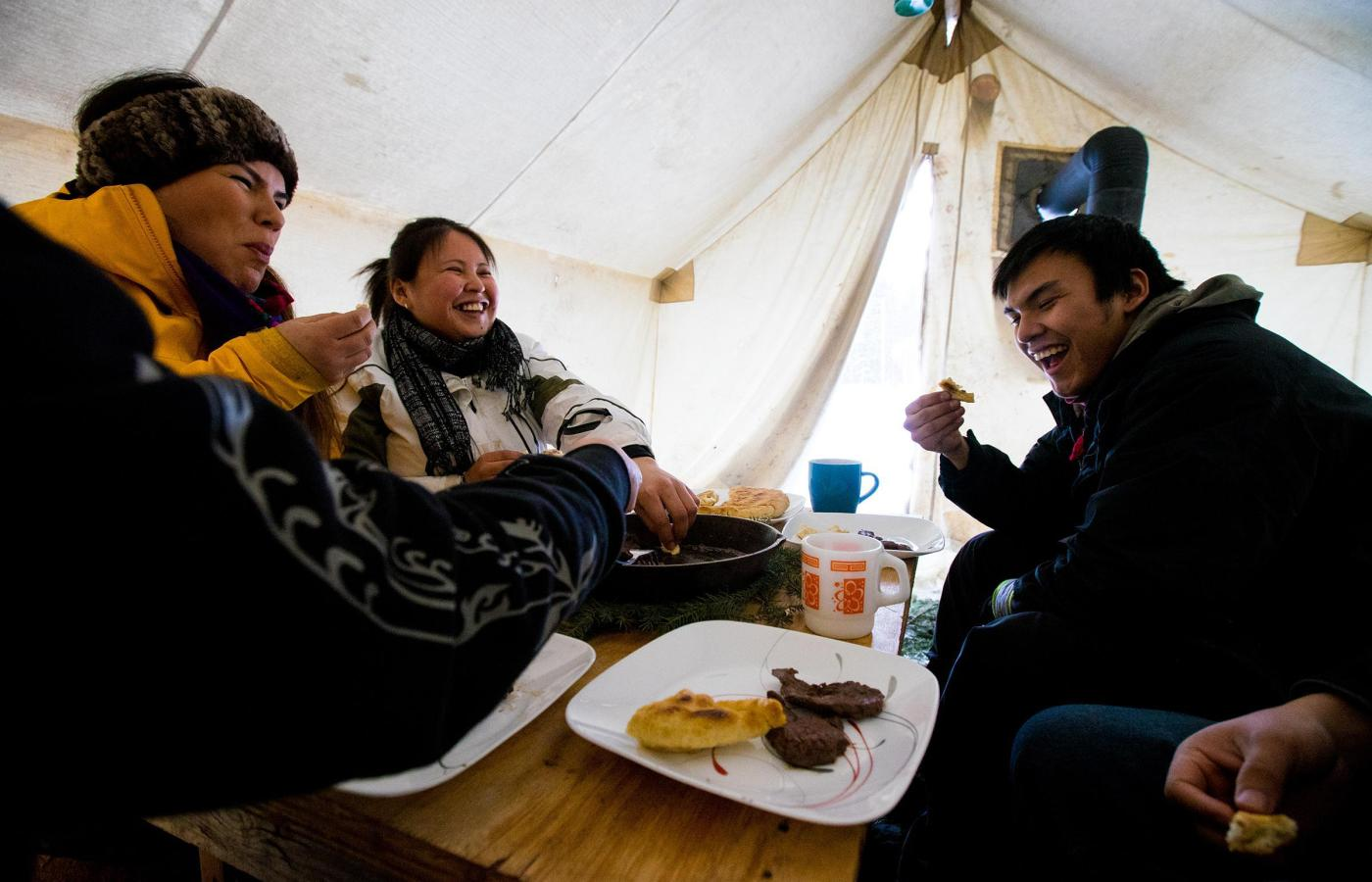 Eating bannock in a wall tent in a Dene camp near Nahanni Butte