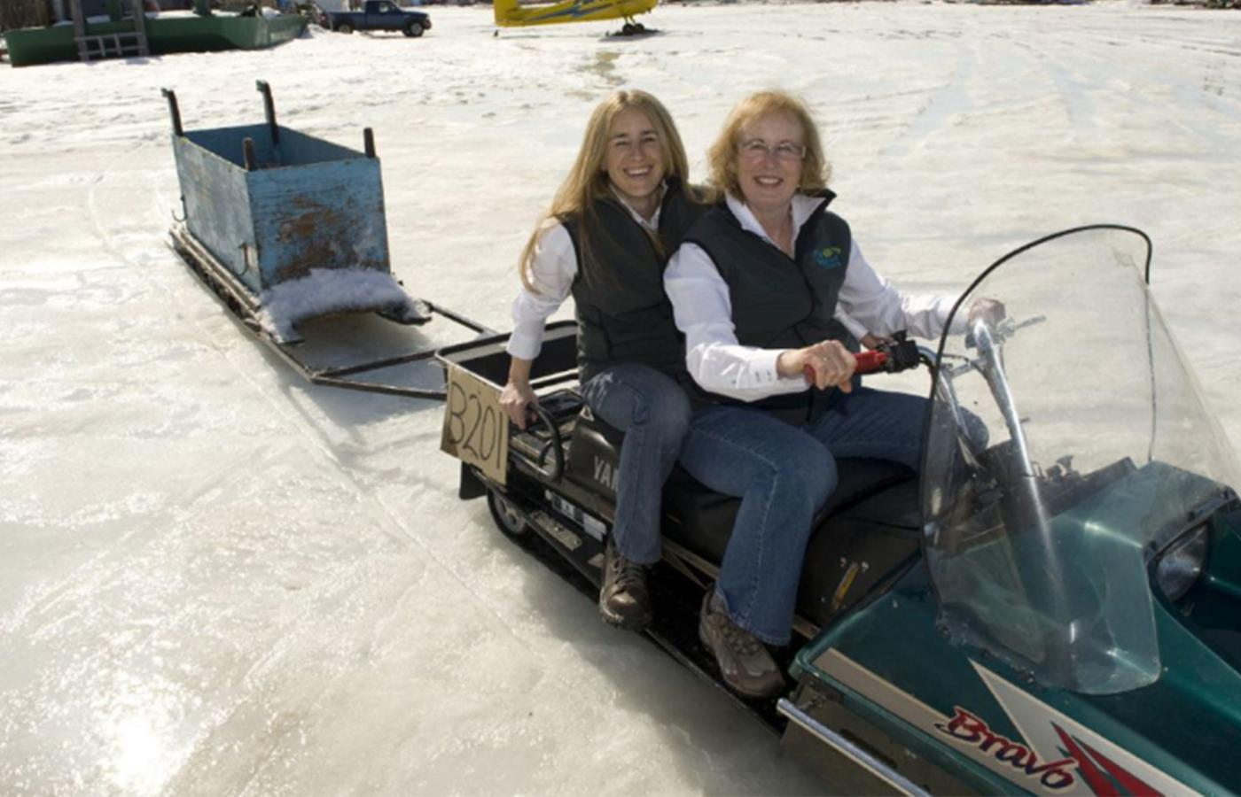 two women sitting on a ski-doo that's pulling a sleigh are similing in the winter