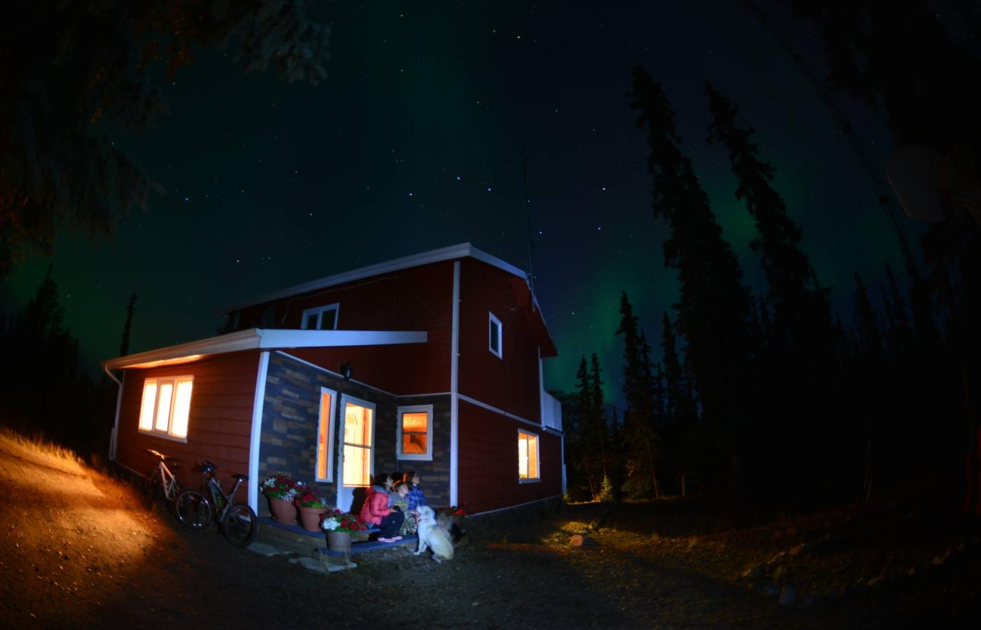 A family watches the Northern Lights from the steps of their cabin
