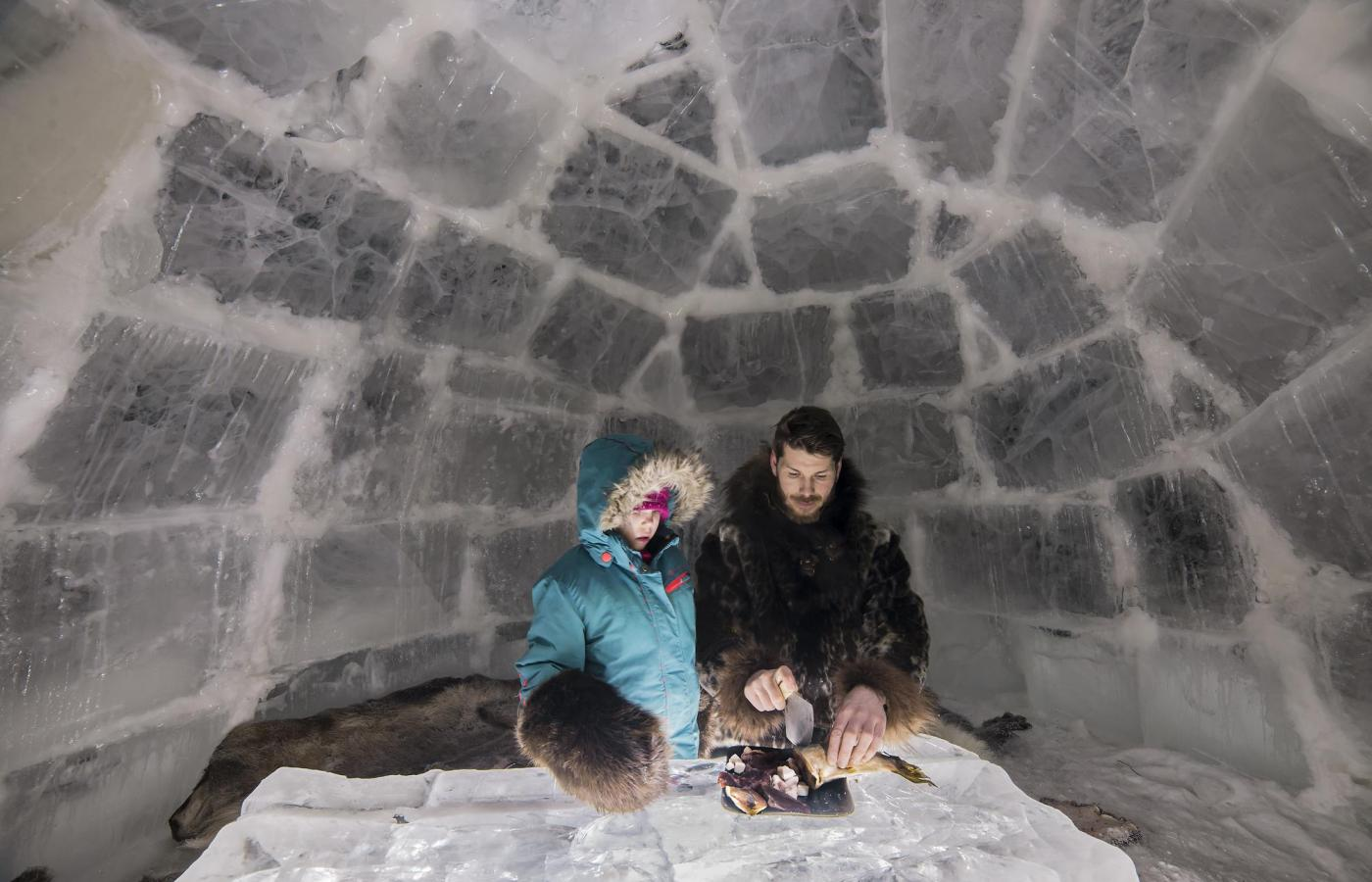a man and a child huddle in an igloo preparing a meal