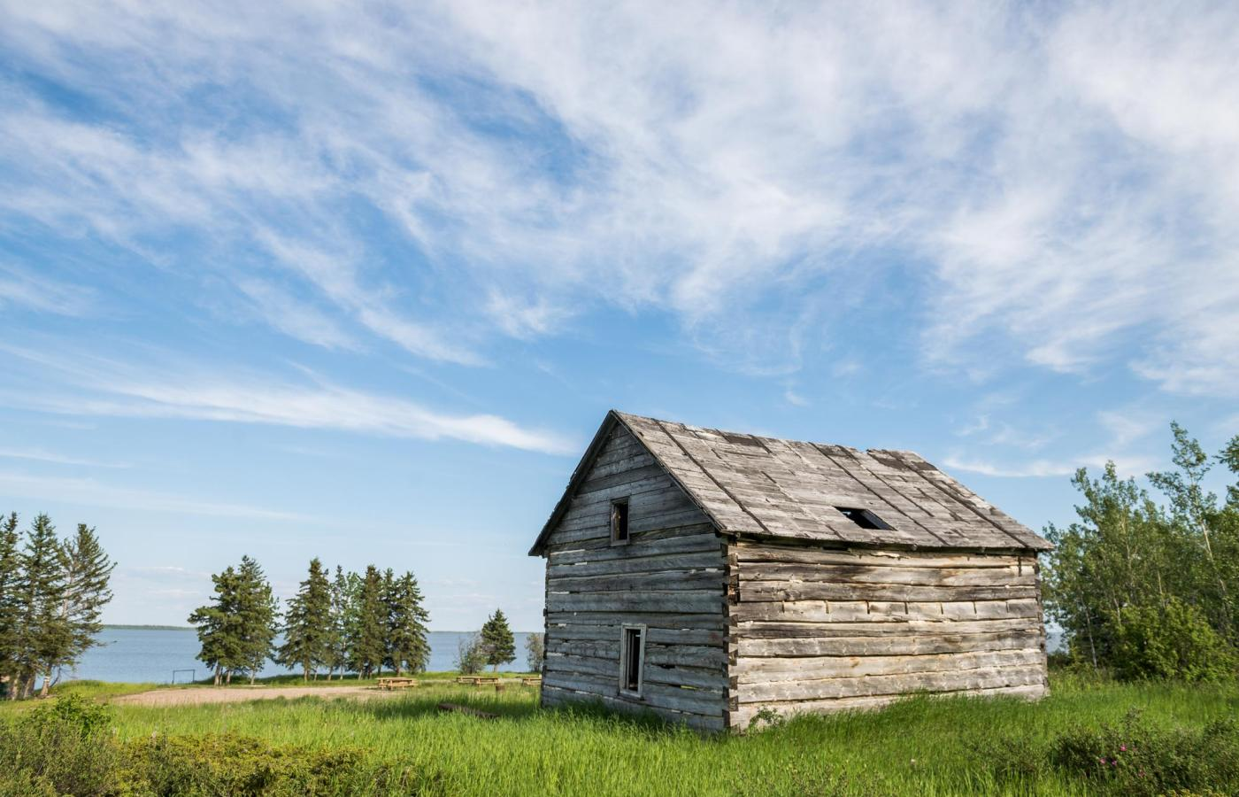 The historic hudson's bay company trading post stands weathered against a blue sky.