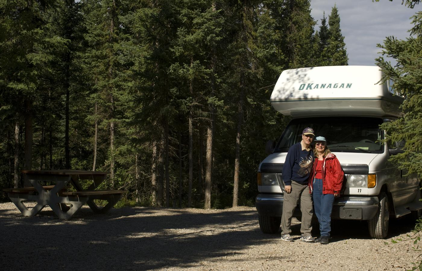a retired couple pose in front of their RV at a Hay River campground