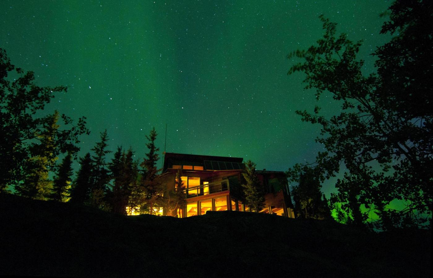 The northern light dance above a wood cabin perched on the Northern landscape