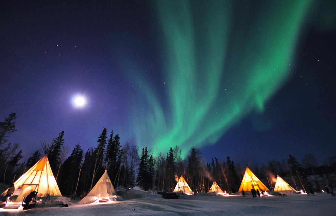 The green northern lights dance above glowing teepees in the snow