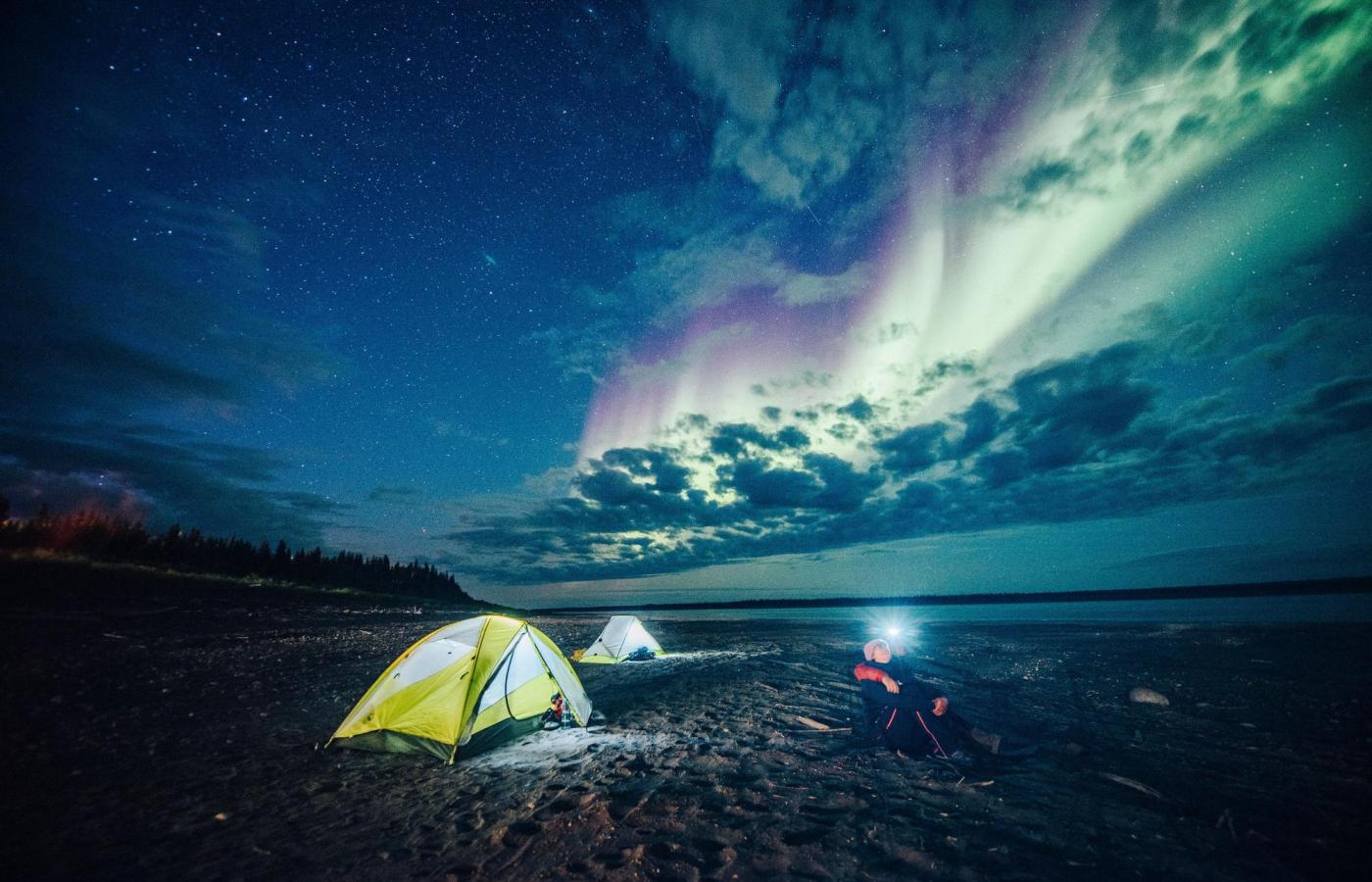 a person sits on the beach next to a tent watching the northern lights overhead