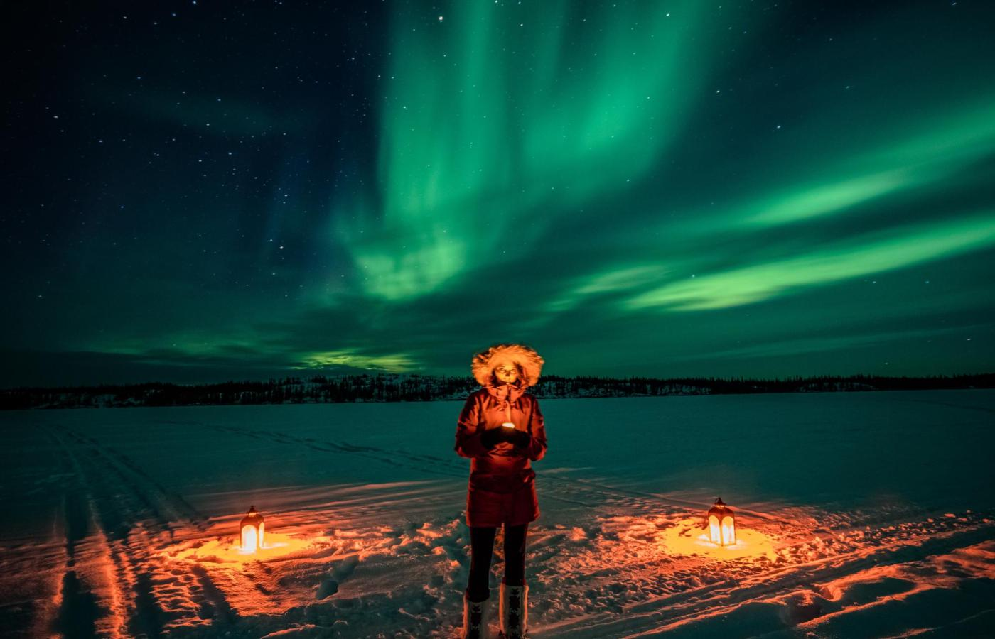 A woman in a parka holds a lantern in the snow as the northern lights shine bright