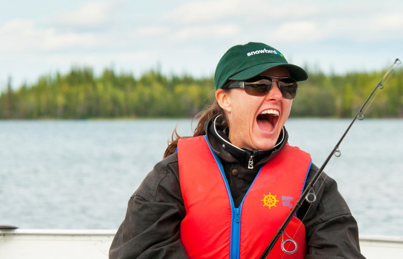 a woman smiles while fishing in a boat in the Northwest Territories