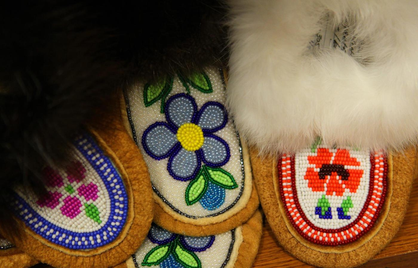 A stack of Dene style beaded moccasins depicting local flowers
