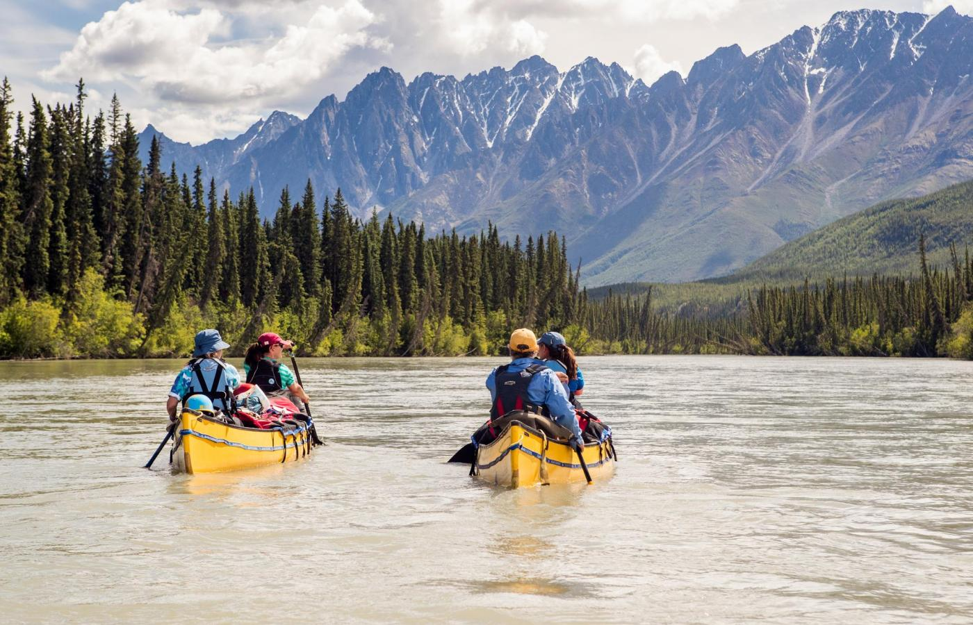 two canoes paddle down the nahanni river with mountains looming in the background