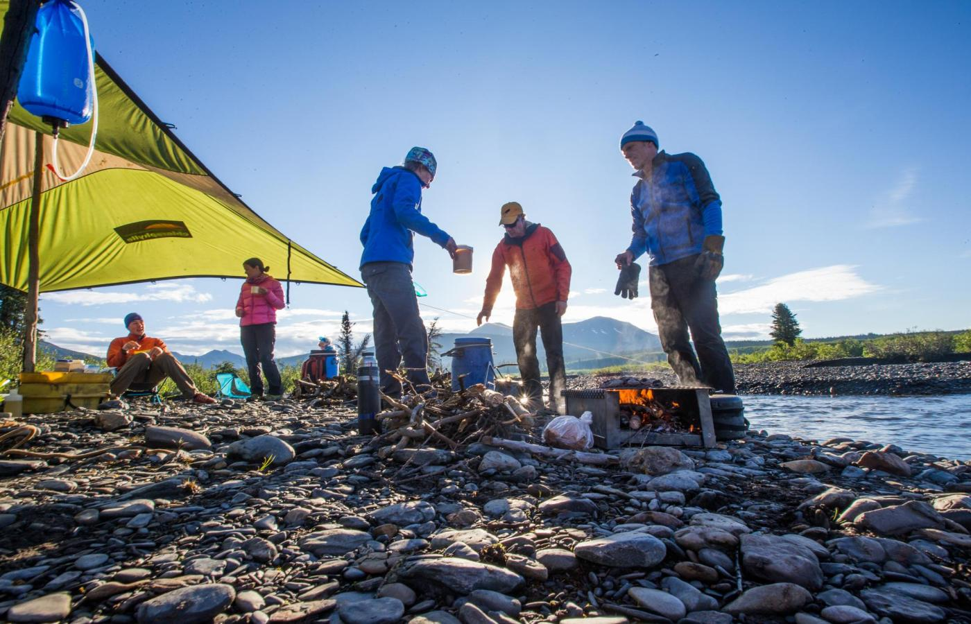 a group of people set up camp on the shores of the nahanni river