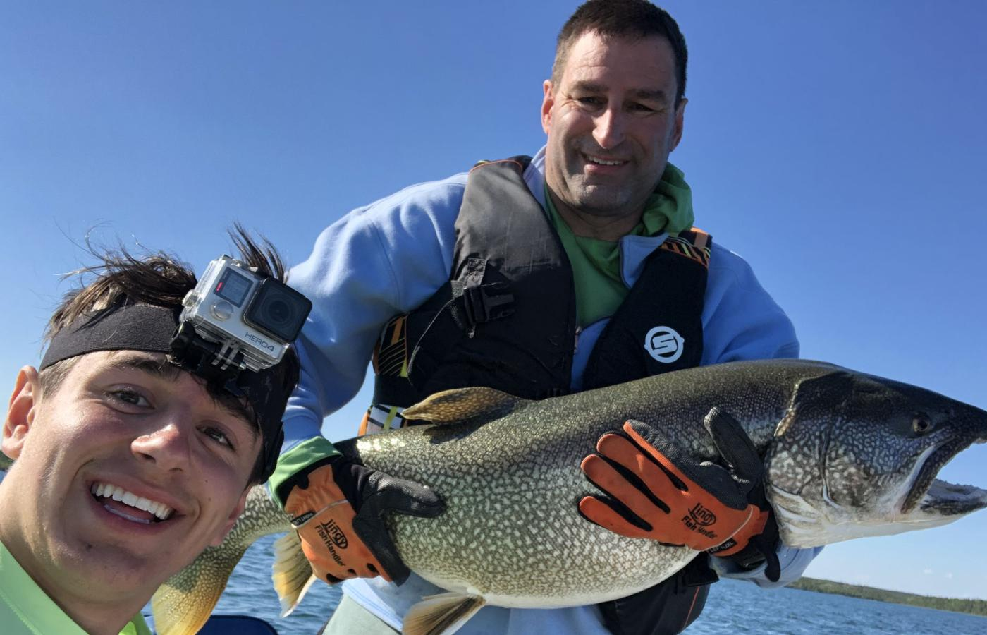 A man and his son pose for a selfie after catching a fish in the NWT