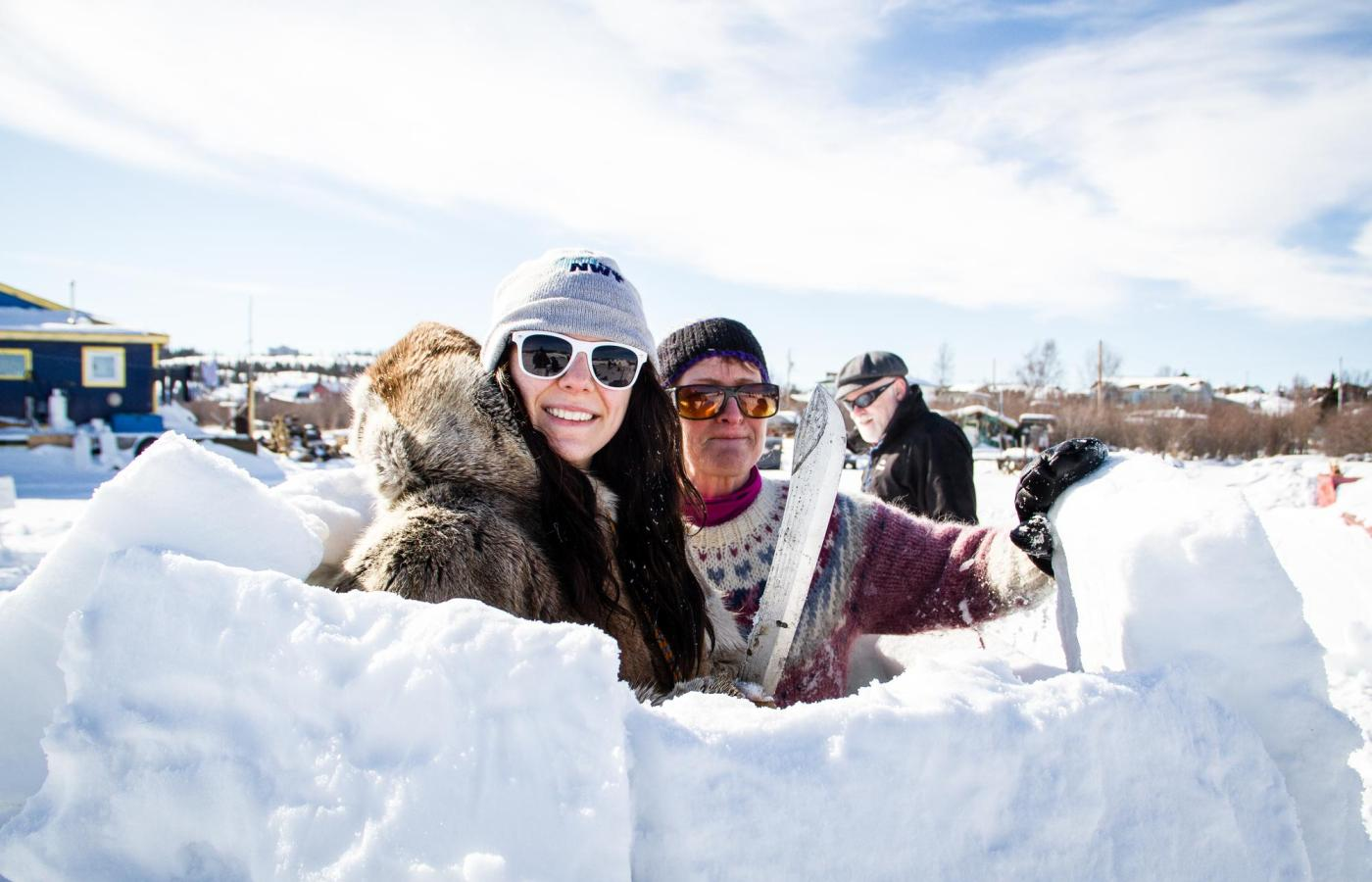 two people smile while they build an igloo at the long john jamboree