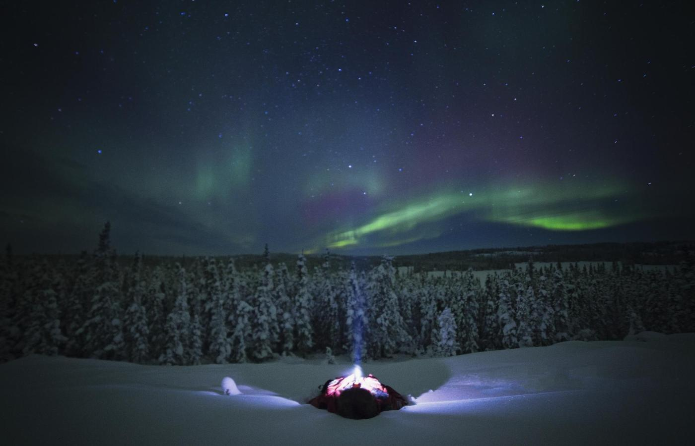 a person lies in the snow watching the aurora