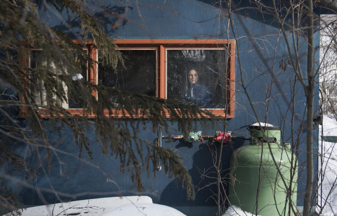A Northwest Territories resident looks out their snowy cabin window