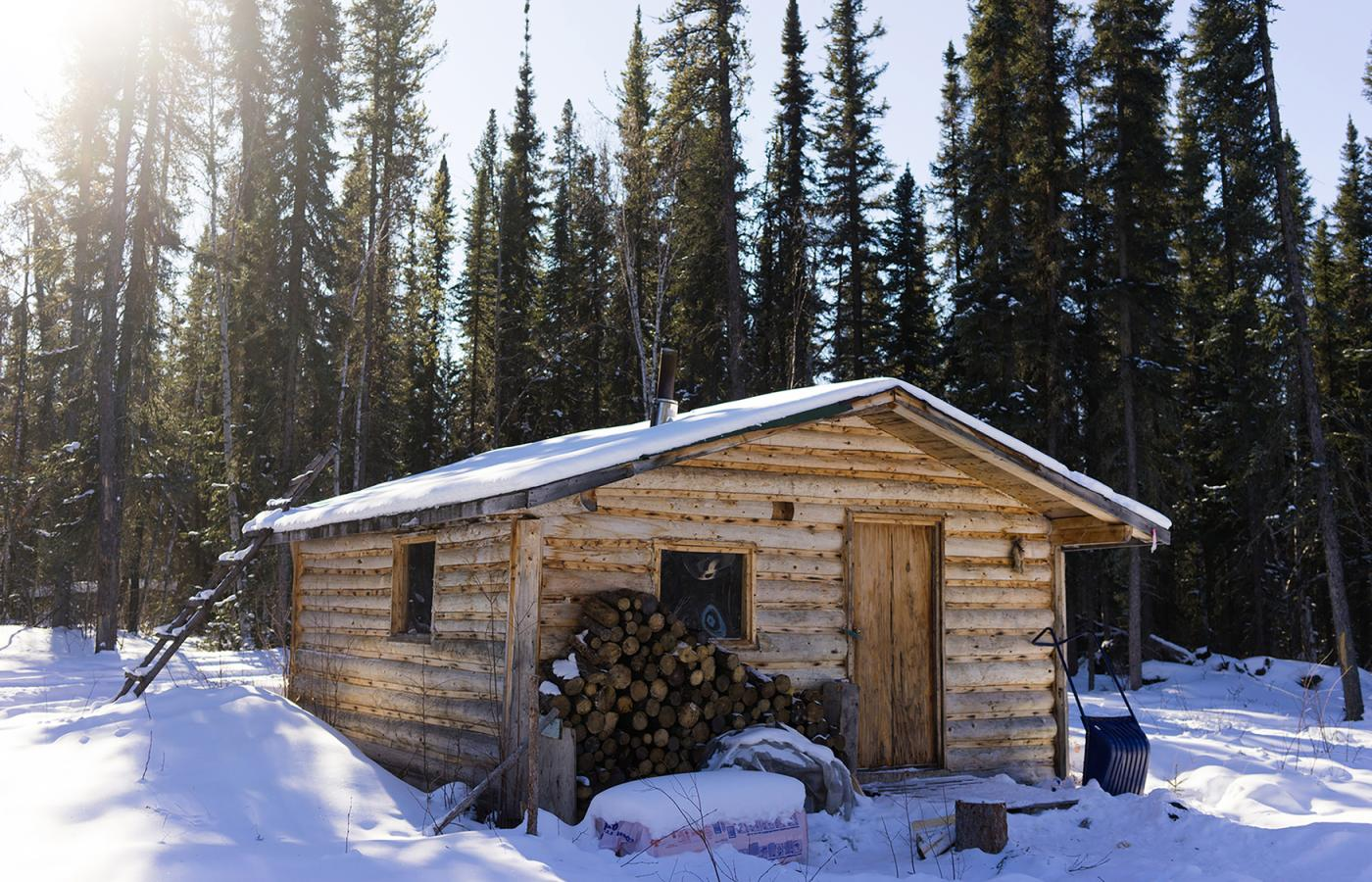 A snowy log cabin on a sunny day in the Northwest Territories