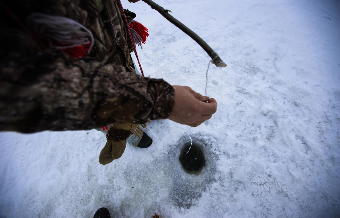 A person checking their ice fishing line in the NWT