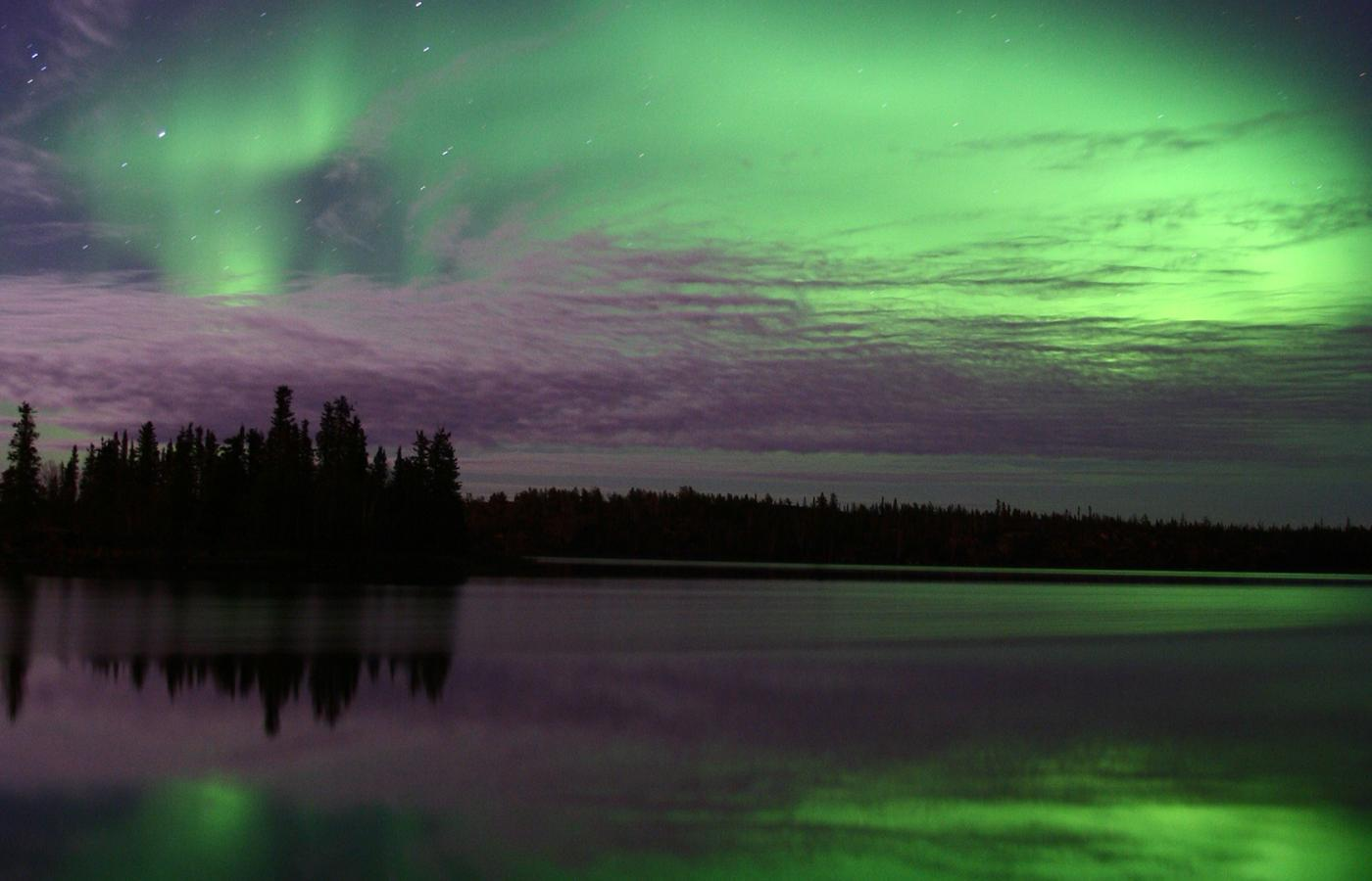 Northern Lights in the night sky above a placid lake in the Northwest Territories, photo credit Aurora Village