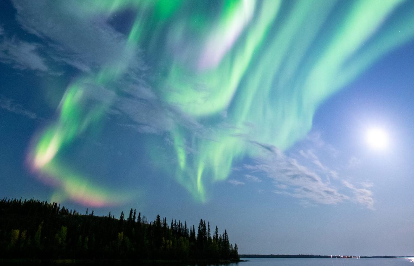 The Northern Lights dance in the night sky over a lake in the Northwest Territories.  Photo Credit Bill Braden