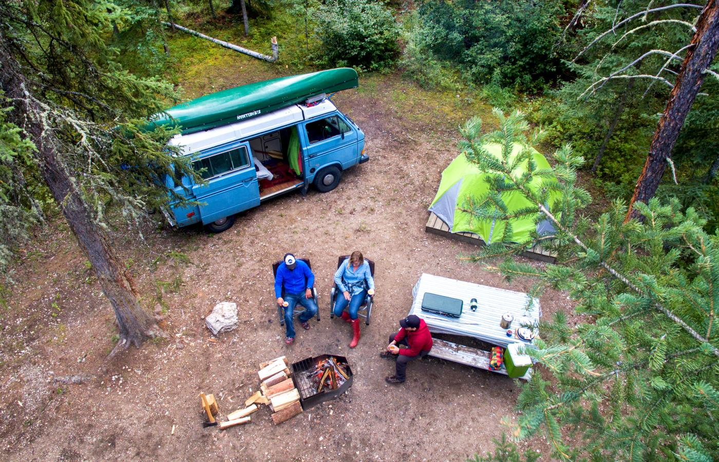 An aerial view of 3 people sitting around a fire pit camping in the Northwest territories