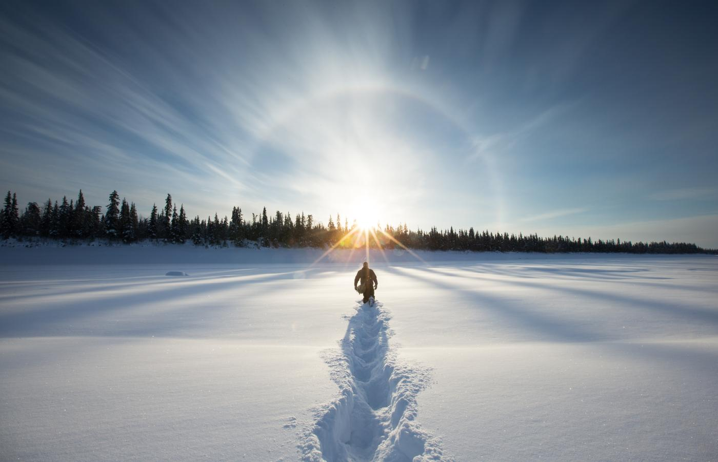 A person breaks trail through the snow toward a sundog in the Northwest territories