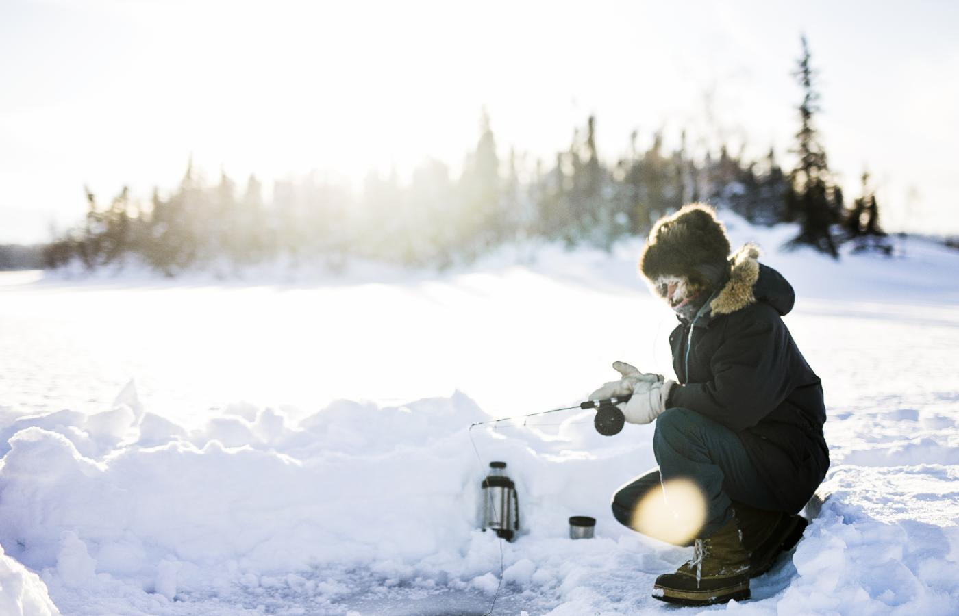 a person ice fishes on a frozen lake in the Northwest Territories