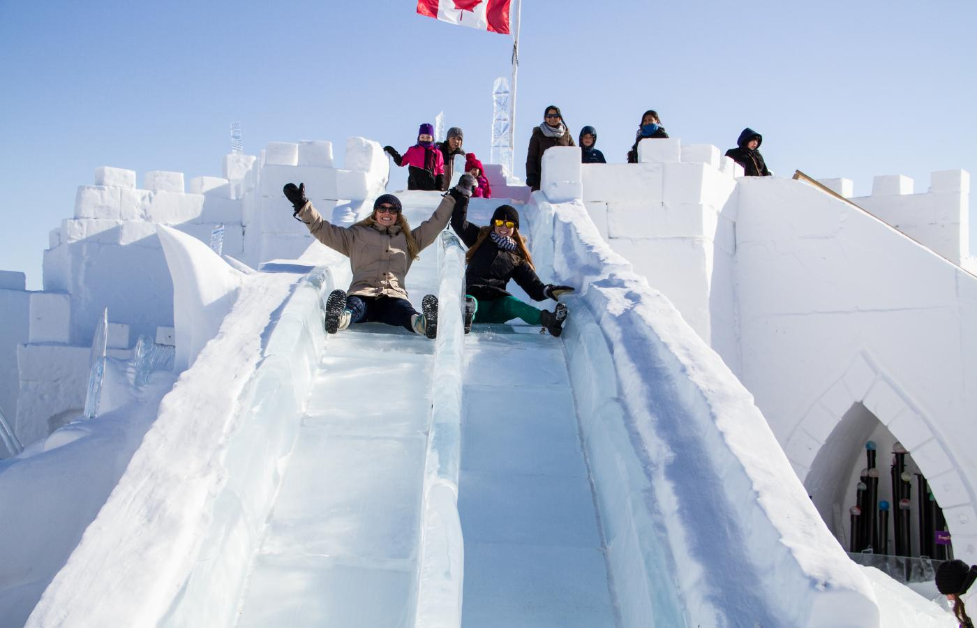 2 people slide down a tandem ice slide at the snowking festival on the great slave lake in the Northwest Territories