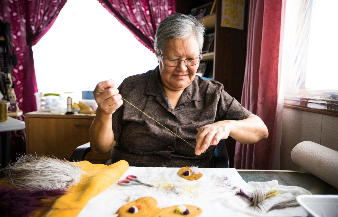 a craftswoman works with caribou hide and tufts in the Northwest Territories