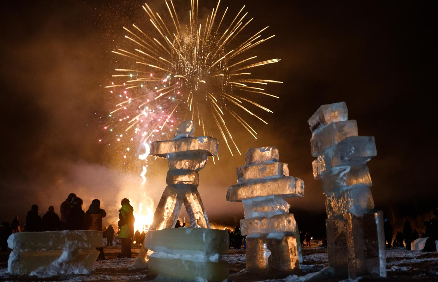 Inukshuks stand in the foreground while Fireworks explode in the night sky at the Inuvik Sunrise Festival.  NWT