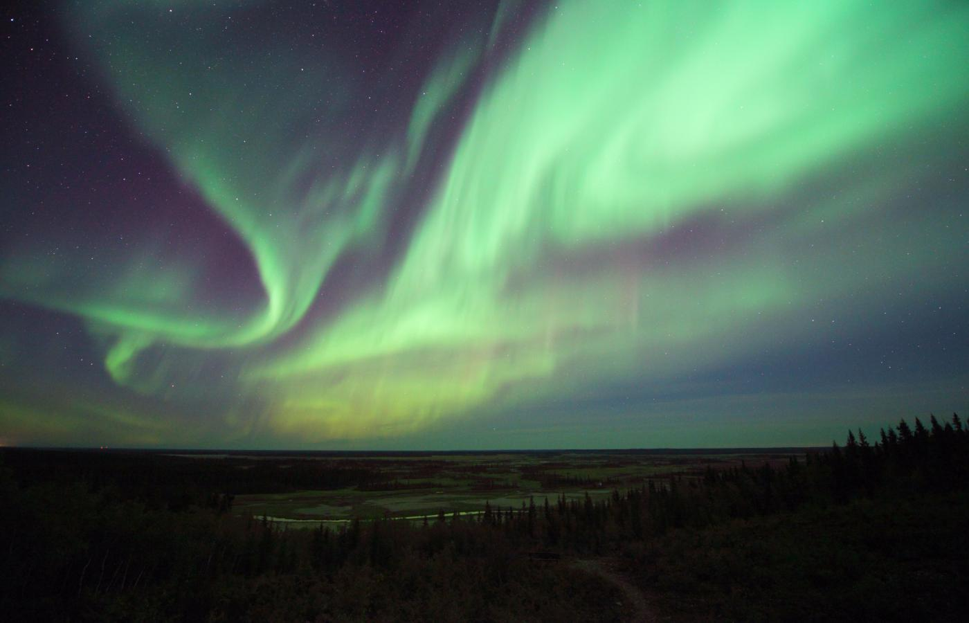 The green blue and purple of the aurora dance in the sky above a lake in the Northwest Territories